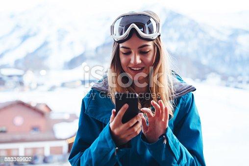 young  snowboarder woman at ski resort village