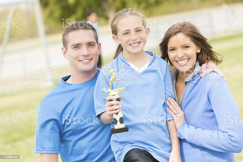 Young soccer champion holding trophy with her parents stock photo