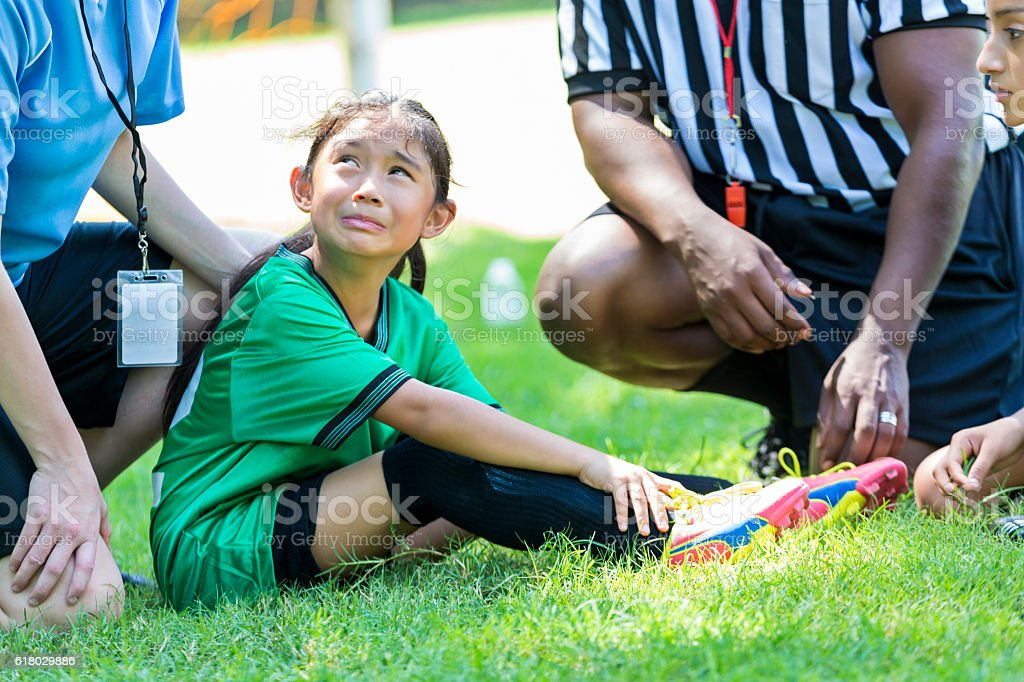 Young soccer player cries after injuring ankle stock photo