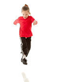 Studio capture of young girl wearing red tee shirt and black athletic pants and cleats. She is running, looking down, and going though a kicking motion, in mid air. Studio isolated, reflection left in as a visual queue that the girl is in mid-air. Easily used as a design element.