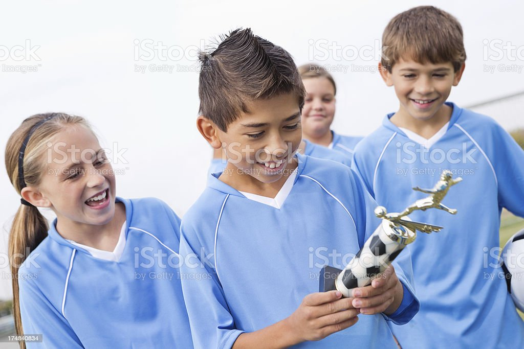 Young soccer player looking at his winning trophy royalty-free stock photo