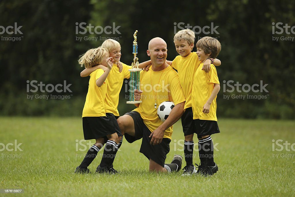 Young Soccer Players Celebrating Victory With Coach royalty-free stock photo