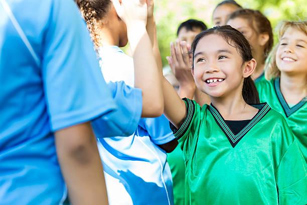 young soccer team gives opposing team high fives after game - kinder die schnell arbeiten stock-fotos und bilder