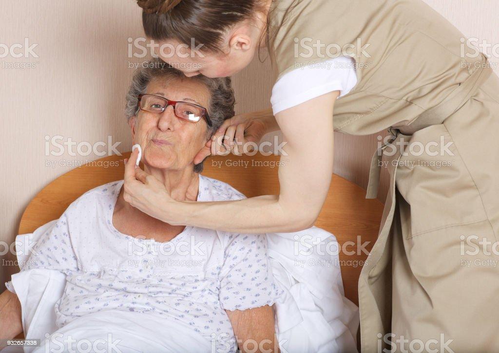 Junge Sozialarbeit Assistent kümmert sich um eine ältere Frau zwischen 70 und 80 Jahre alt. – Foto