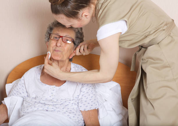 Young social work assistant takes care of a senior woman between 70 and 80 years old. stock photo