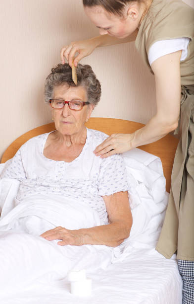 Young social work assistant takes care of a senior woman. stock photo