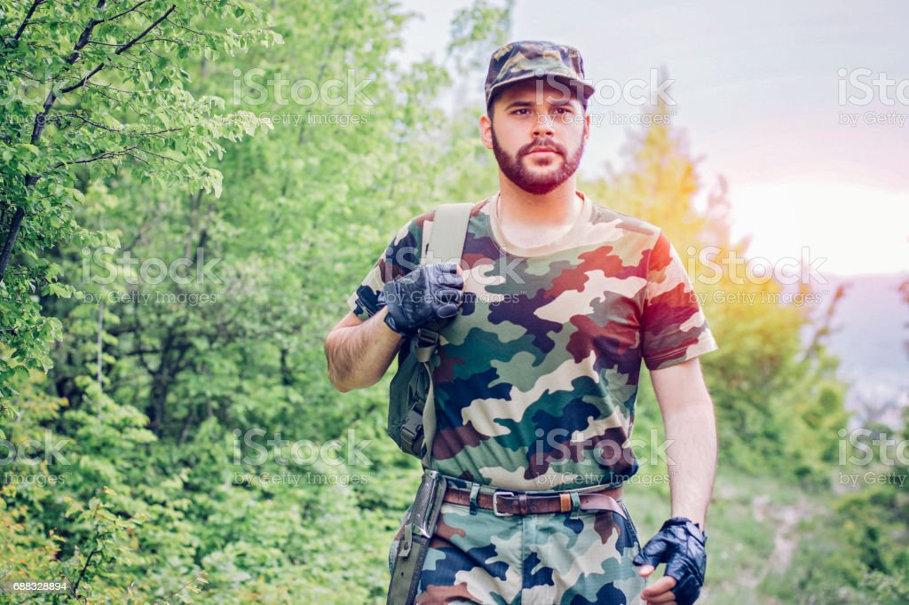 Young soldier walking through forest stock photo