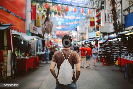 Rear view image of a young man, solo traveler, walking in the Chinatown district of Kuala Lumpur, Malaysia. He is wearing a white rucksack, enjoying walking and shopping in Malaysia capital.
