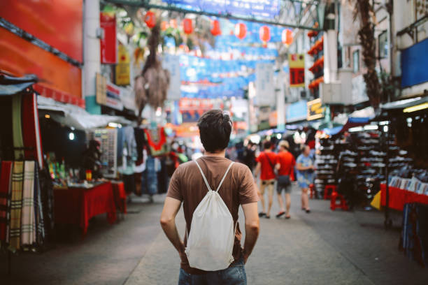 Young solo traveler in Kuala Lumpur Chinatown district Rear view image of a young man, solo traveler, walking in the Chinatown district of Kuala Lumpur, Malaysia. He is wearing a white rucksack, enjoying walking and shopping in Malaysia capital. explorer stock pictures, royalty-free photos & images