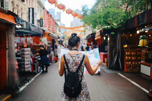 istock young solo traveler woman in Singapore street market checking the map 1086145112