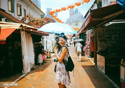 Vintage toned street style portrait of a young brunette woman. She is enjoying the walk and exploring the city, wearing a casual but fashionable dress, sightseeing and shopping on the Singapore street market.