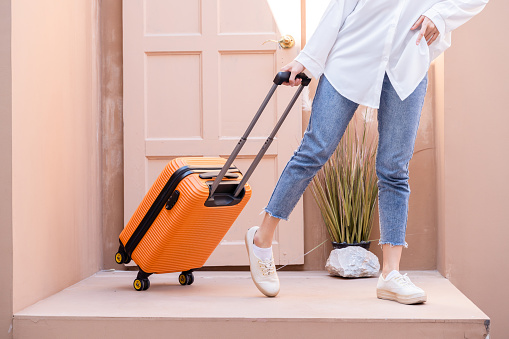 Young solo traveling woman standing with Georgian door as she is towing her bright orange suitcase filled with remote working tech, putting away plane tickets in her left pocket