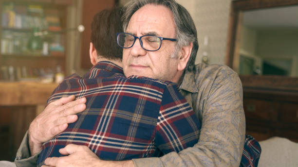 Young son embracing his father with love stock photo