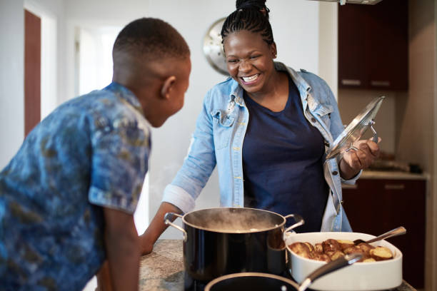 Young Son Watching African Mother Prepare Food stock photo