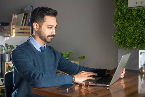 Young south asian man using laptop in office stock photo