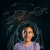 Young girl smiling, imagining she will be an astronaut.