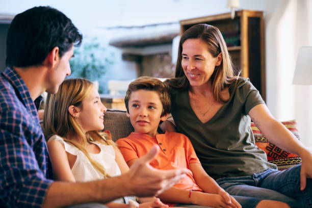 Young Spanish family together on sofa in family home stock photo