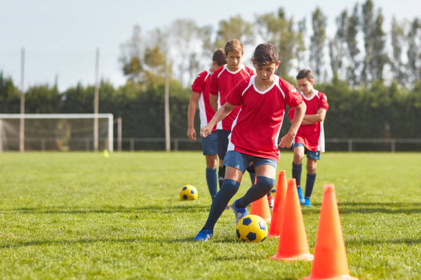 Young Spanish Footballers Dribbling Around Cones in Drill stock photo