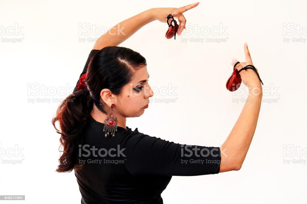 Mulher jovem cigana espanhola dança flamenca com marrons castanholas nas mãos dela. Dançarina de flamenco em lindo vestido nacional sobre um fundo branco. Dançarina de garota de Espanha em roupas tradicionais. Balé. foto royalty-free