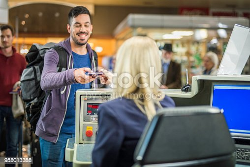 Smiling young hispanic man handing over his passport to an airport employee at a check-in counter.