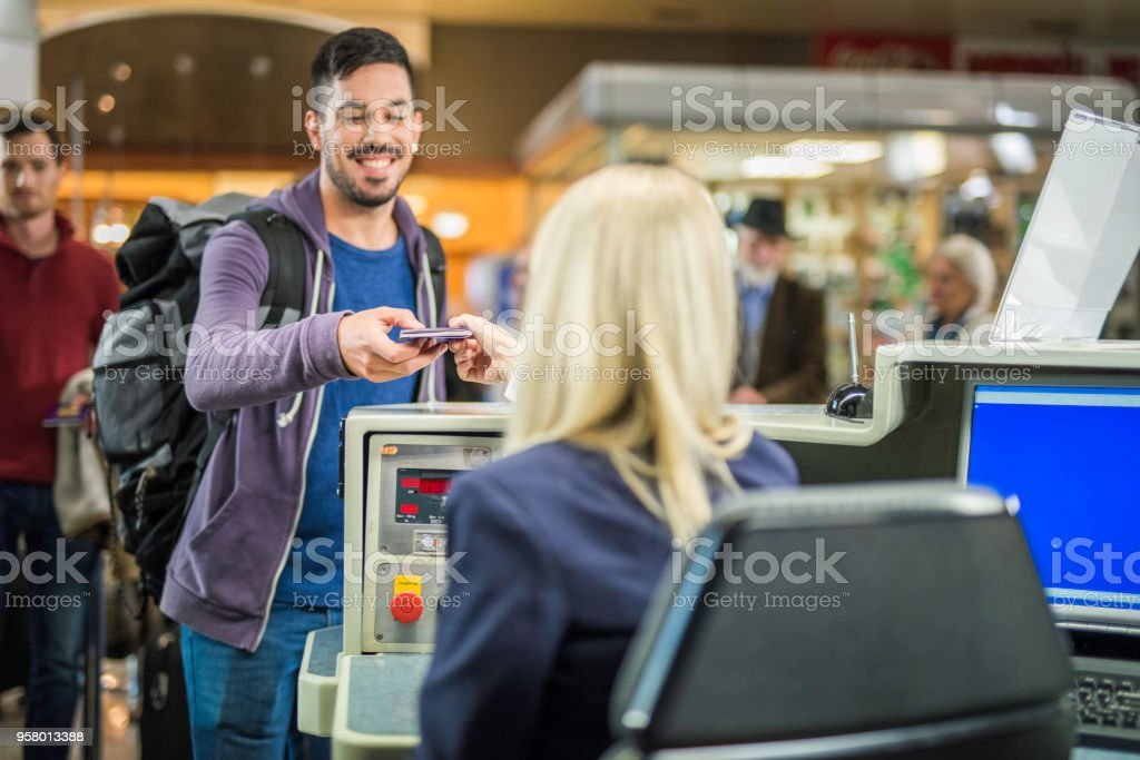 Young spanish man checking in at an airport counter stock photo