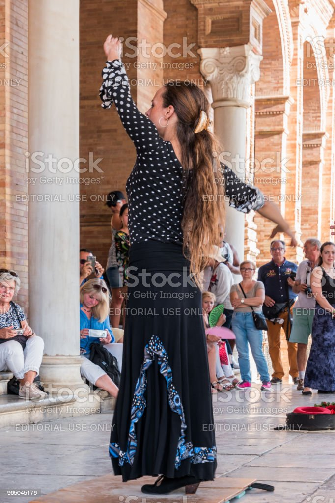 Young Spanish woman dancing Sevillanas wearing the traditional folk dress in flamenco traditional dance of Spain. Performing show in the Plaza of Spain, Seville. royalty-free stock photo