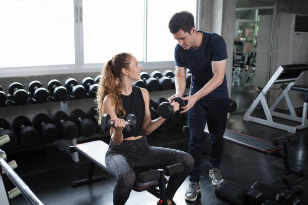 young sport woman exercise lifting dumbbells on the bench in fitness gym healthy .Muscular girl in sportswear training biceps  with personal trainer man workout.bodybuilding stock photo