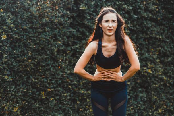 Junge Sportlerin mit Schmerzen im Bauch. Konzept der Gesundheit Problem. – Foto