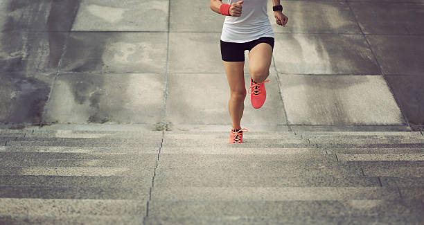young sport woman running upstairs on city stairs - endurance stock photos and pictures