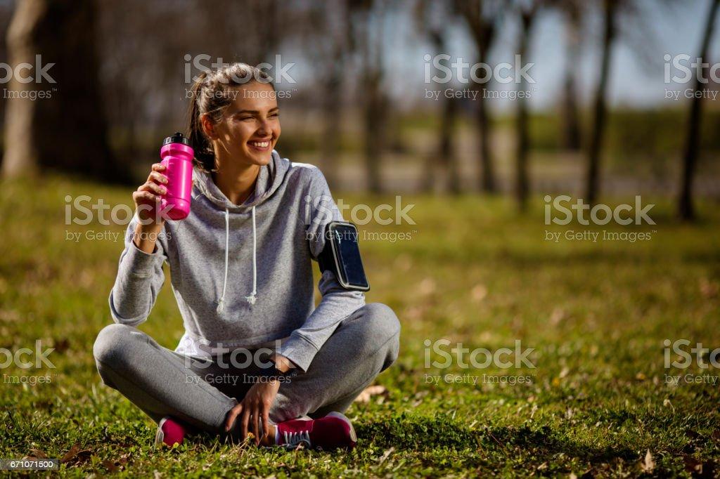 Joven mujer sentada en el suelo del deporte - foto de stock