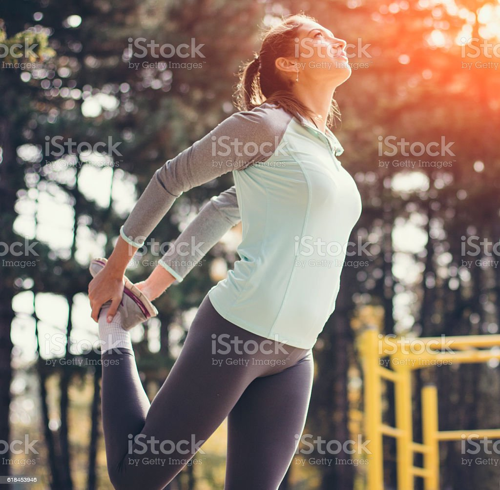 Young sport woman stretching in park stock photo