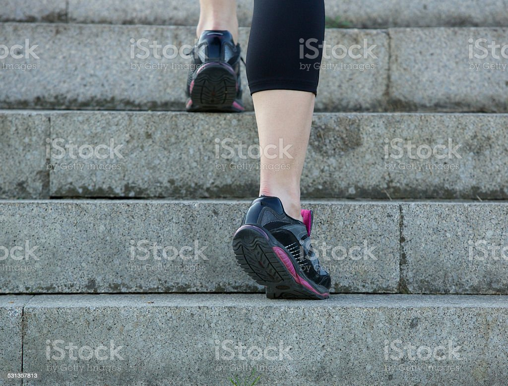 Young sport woman walking upstairs in gym shoes stock photo