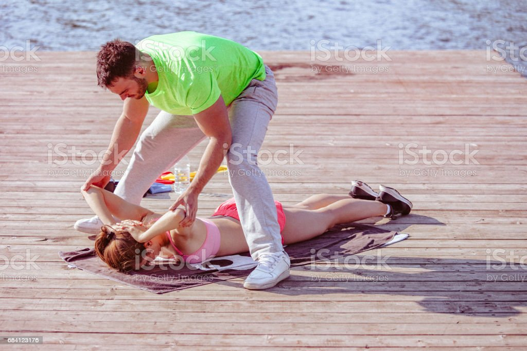 Young sporting woman exercises outdoors with help of personal trainer foto stock royalty-free