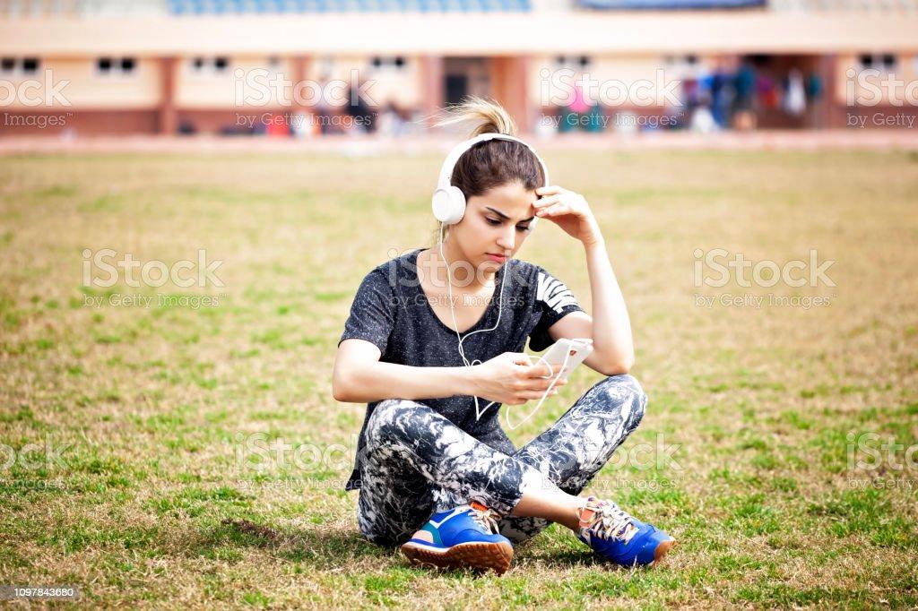 Sportif kadın kulaklık ile müzik dinlemek stok fotoğrafı