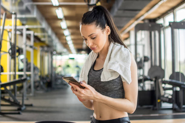 Young sportive woman using phone after training in gym stock photo