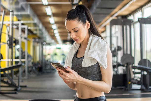 Junge sportliche Frau mit Demtelefon nach dem Training im Fitnessstudio – Foto