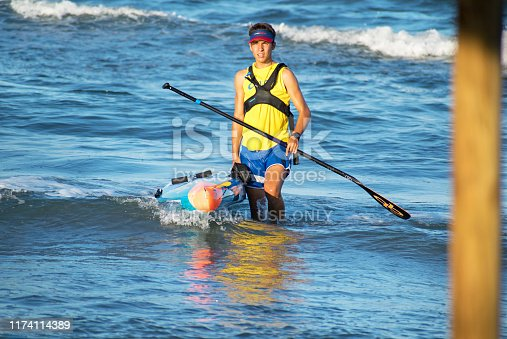 Barcelona, Spain, August 18, 2019: Young sportsman kayaking at the seashore during summertime