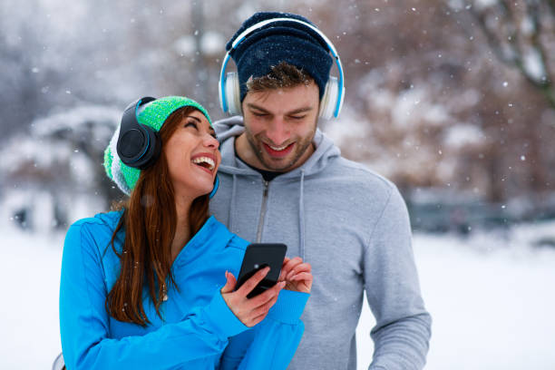 Young sports couple resting after jogging on snowy day in the city stock photo