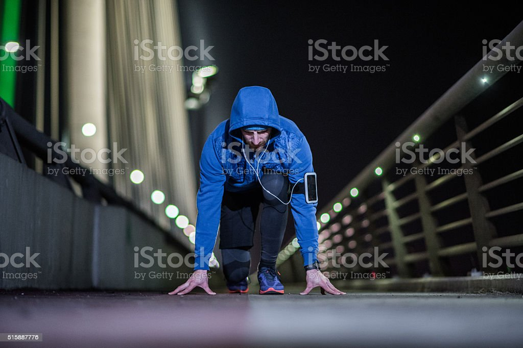 Young sports man in start position preparing to run stock photo