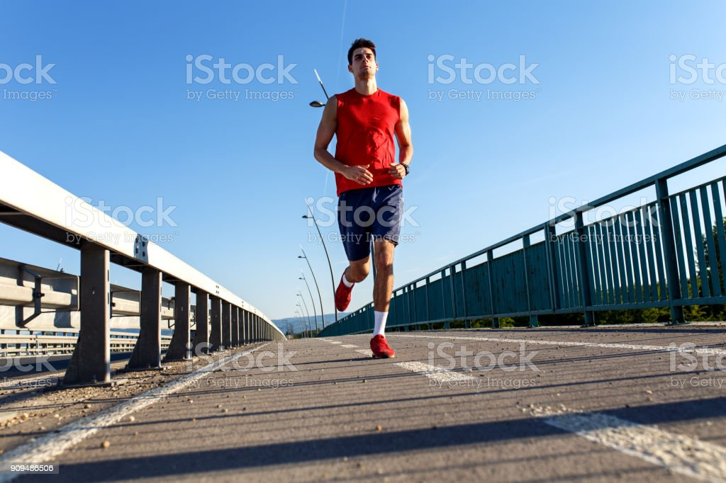 Young sports man running on bridge. stock photo