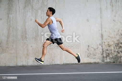 young sports man running outdoors in front of concrete wall