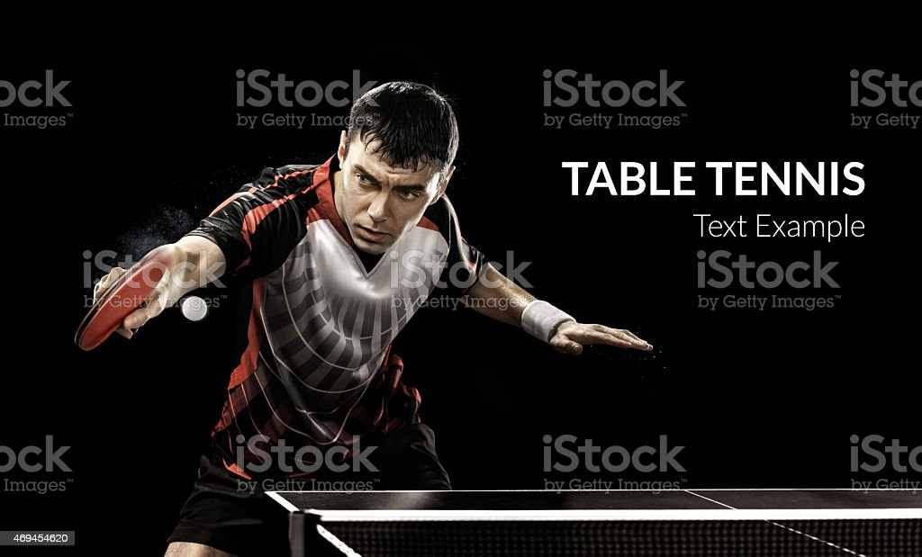 Young sports man tennis-player in play on black background stock photo