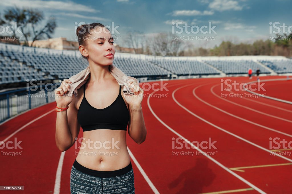 Young sports woman after workout with towel on his shoulders on the stadium after runing workout stock photo