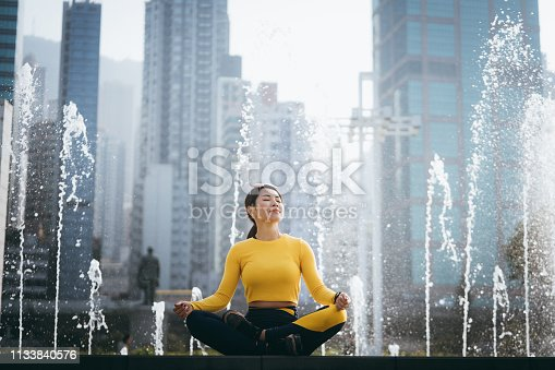 Young sports woman meditating in urban park in city, with modern city skyline as background