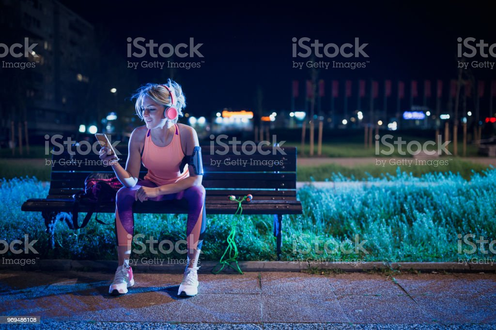 Young sports woman resting after training, listening music and using mobile phone stock photo