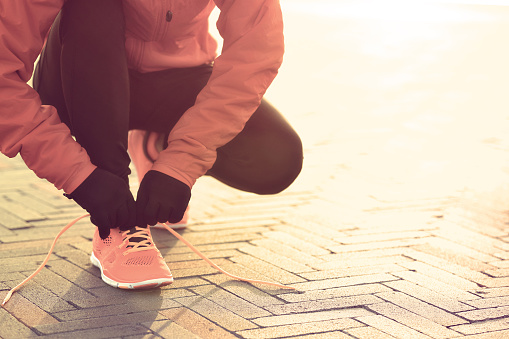 young sports woman runner tying shoelace at sunrise