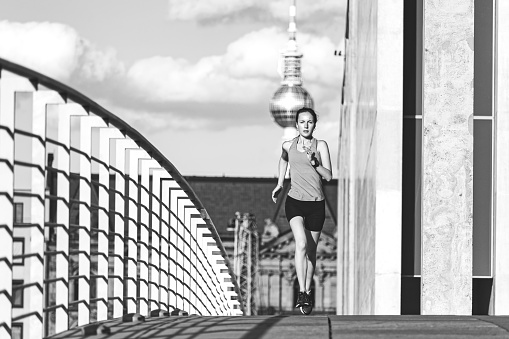 istock young sports woman running in Berlin 1172696346