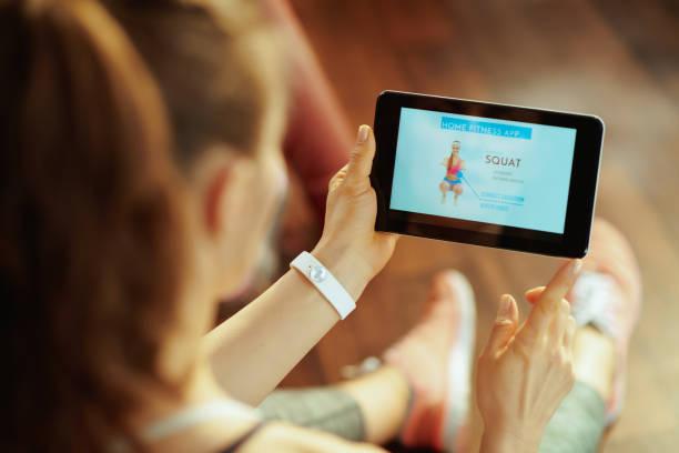 ung sport kvinna som använder hem träning tränare app i tablet pc - calendar workout bildbanksfoton och bilder