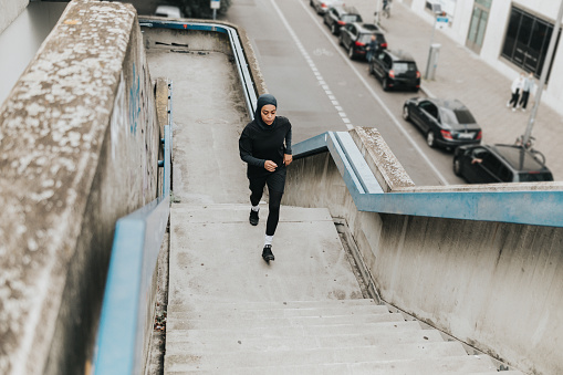 high angle view on young muslim sports woman with sports hijab running up concrete stairs  in Berlin