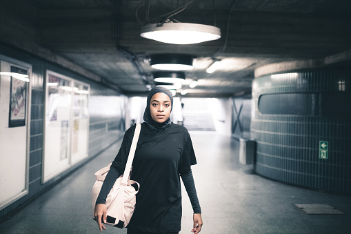 young muslim sports woman with hijab standing in subway station in Berlin and looking to camera